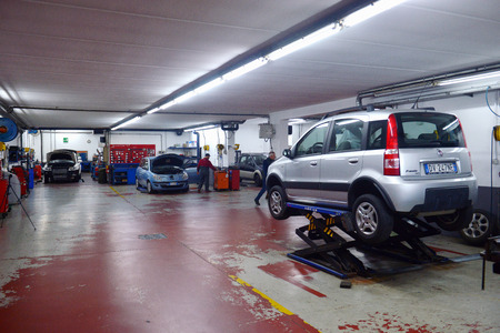 Italy, Desio, 26 october, 2018, Car technician repairing car in workshop service station,  Italy, Desio, 26 october, 2018
