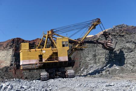 Bagger arbeitet mit Granit oder Erz im Tagebau Standard-Bild