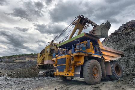 Gran camión volquete de cantera. Cargando la piedra en el dumper. Carga de carbón en camión de carrocería. Camión de minería maquinaria de minería, para transportar carbón desde cielo abierto