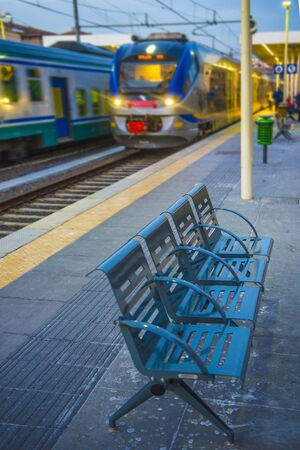 Picture of bench on the train station with blurred train on the background