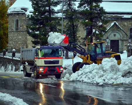 Snow cleaning tractor snow-removal machine loading pile of snow on a dump truck. Snow plow outdoors cleaning street city after blizzard or snowfall