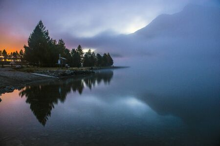 fog over a mountain lake before dawn. The combination of moonlight and sunlight
