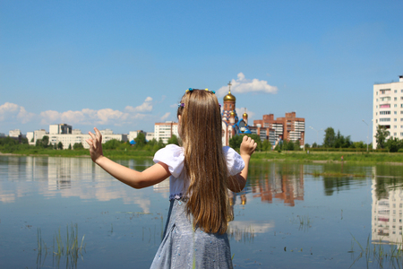 Girl seven years is streching out her hands and standing on the lakeshore Stock fotó