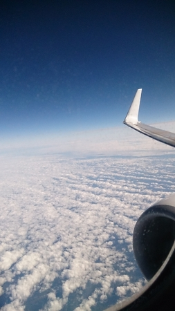 the plane is flying, below the clouds