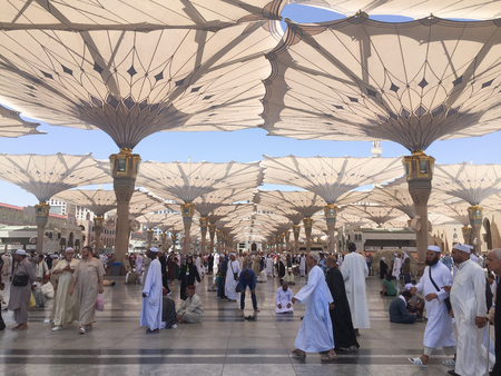 MEDINA, SAUDI ARABIA - APRIL 19, 2016 : Muslim Devotees Resting And Praying Under The Giant Retractable Tent At Prophet Muhammad Mosque In Medina