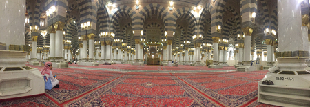 MEDINA, SAUDI ARABIA - APRIL 19, 2016 : An Arab Muslim Waiting For Prayer Time In The Prophet Muhammad Mosque In Medina In Panorama Mode. Al-Masjid An-Nabawi (Prophets Mosque) Is A Mosque Established And Originally Built By The Prophet Muhammad PBUH, Sit