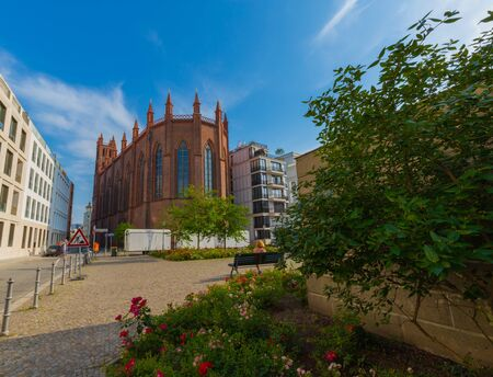 Berlin Germany - June 2019: 1800's Neo-Gothic brick church from behind on a sunny afternoon next to modern architectures. Editorial