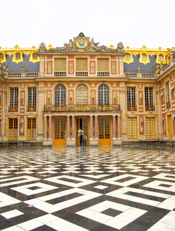 louis the rich heritage: Checked floors and gilded decor at the entrance to Versaille Palace in France.