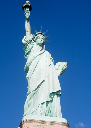 The Statue of Liberty on a sunny day in the harbor of New York City. Stock Photo