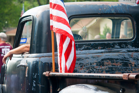 An American flag is attached to the back of an old, beat up pickup truck driving in an Independence Day Parade. Stock Photo
