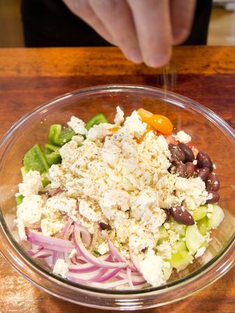 adding: Man adding ingredients to a Greek salad.