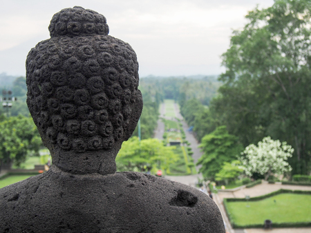 The back of the head of a Buddha statue looking out over Borobudur Temple in Indonesia. Stock Photo