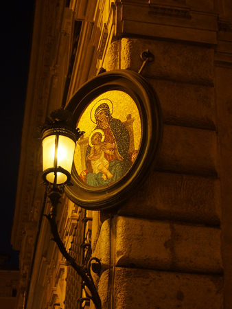 catholocism: A little madonna or madonnelle lights up a street corner at night in Rome Italy.
