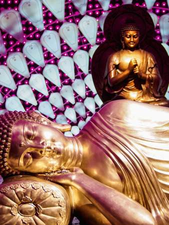 A gold reclining Buddha with purple lights in background.