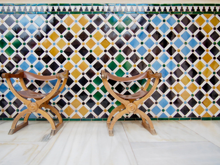Two leather chairs in front of a colorful tiled wall.