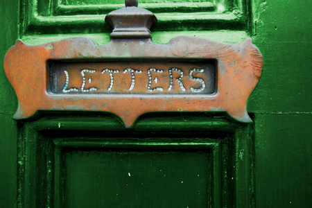 A copper letters slot on a green door. Stock Photo