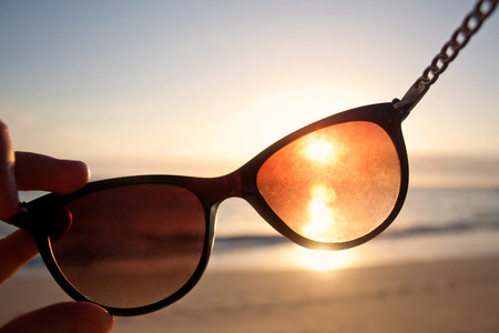 View through a pair of sunglasses at sunset on the beach.