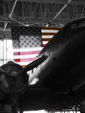 A vintage black and white airplane in a hanger with the American flag. 報道画像