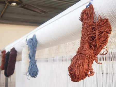 Skiens of natural dyed yarn hanging on a loom.
