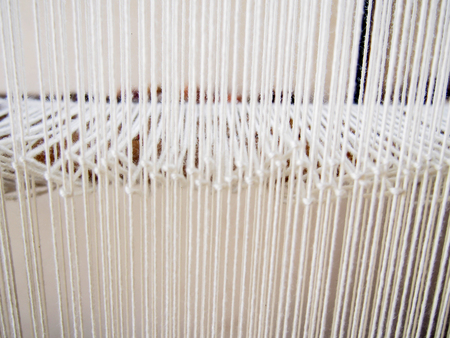 Many strands of white yarn on a loom make a bright, pleasant pattern.