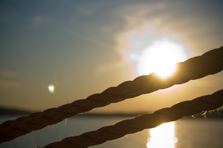 Detail of ropes on a sailboat of the coast of Maine with the sn setting in the background.