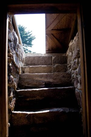 View of the door and stairs from inside a root cellar on a traditional American homestead in Maine. Standard-Bild