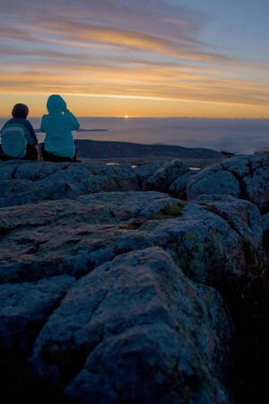 Two tourists watching the sun rise over Acadia National Park from Cadillac Mountain in Maine.