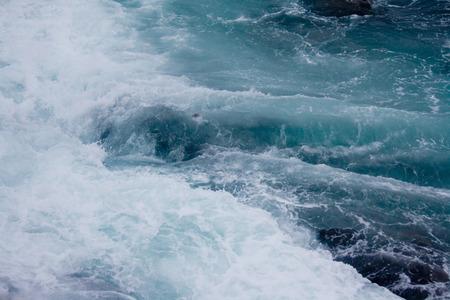 Ocean waves crash against the rocky shore of Maines coast near Bar Harbor.