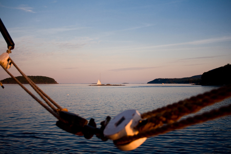 Sailboat in the background on the ocean with ropes in the foreground off the coast of Bar Harbor, Maine. Stock Photo