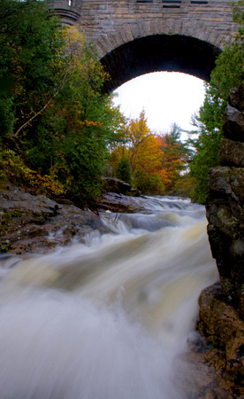 rushes: A river rushes under an arched stone bridge Stock Photo