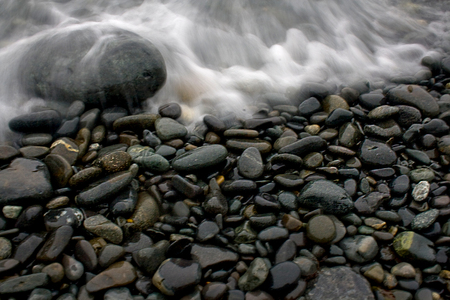 Stones smoothed by the waves on a beach with a wave blurred by long exposure time near Bar Harbor, Maine. 写真素材