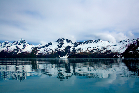 Landscape of mountains being reflected in the blue waters of Kenai Fjords near Seward, Alaska.