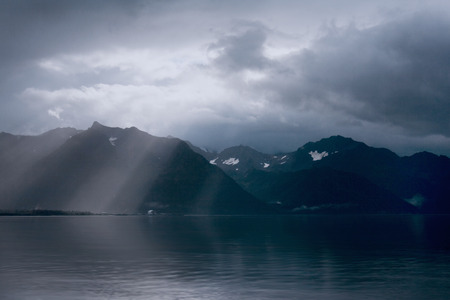Rays of light peak through the clouds in the early morning over the mountains and ocean near Seward, Alaska.