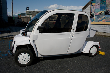 A small white electric car pligged in to charging station.