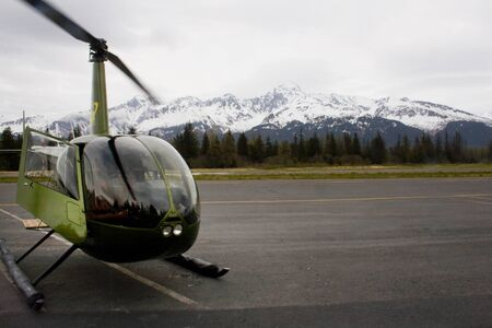 A small green helicopter preparing to take off in Seward Alaska with mountains in background.