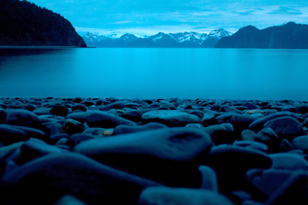 Smooth beach stones on the shore in the foreground of a landscape photo overlooking the ocean and mountains in Seward Alaska at midnight.