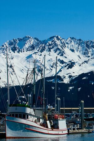 A small red and white boat docked in the harbor in Seward, Alaska.