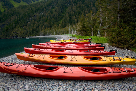 Bright orange and red sea kayaks in a row on the shoreline near Seward, Alaska.