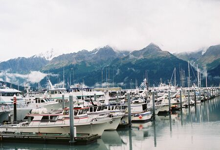 Boats harbored with mountains in the background in Seward, Alaska.