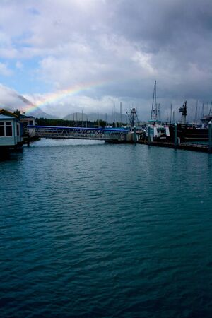 A rainbow forming over the harbor near the city of Seward, Alaska. Editorial