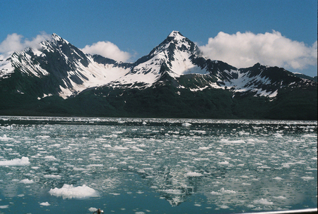 Chunks of ice floating on the ocean water with mountains in the background near Seward, Alaska.