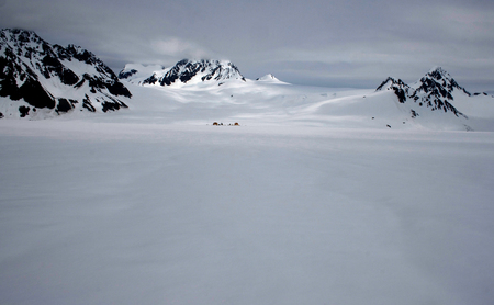 An expansive view of a Glacier in Seward, Alaska with a camp set up in the distance.