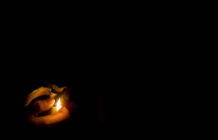 A hand using a lighter to light a fire with a black background.