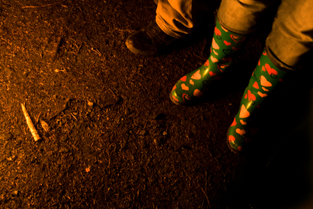 View of the feet of people standing around a fire wearing rain boots with hearts on them at a party. Zdjęcie Seryjne