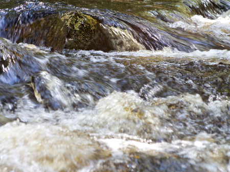A rock with water flowing over it in a rushing river in Bear Brook State Park near Allentown, New Hampshire. Standard-Bild
