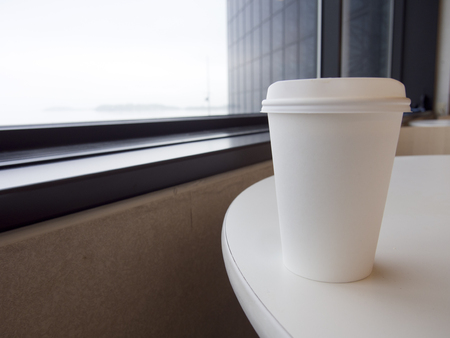 A white paper coffee cup with lid sits on a table near a window. Standard-Bild