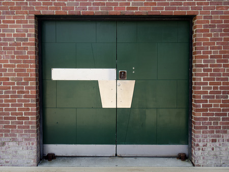 A green painted metal door in an old brick building.