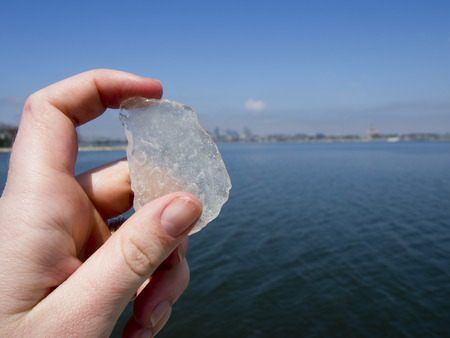 massachussets: A hand holding up a piece of sea glass in front of Boston Harbor in Massachussets. Stock Photo