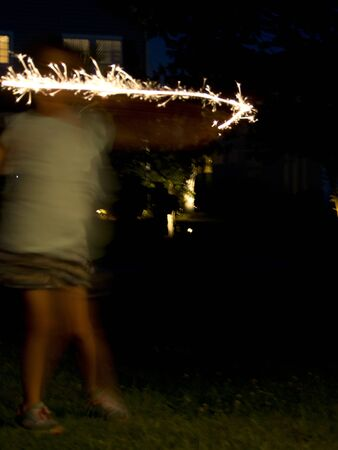 A child dancing with sparklers in the dark creates an abstract image of celebration.