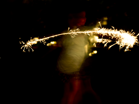 A child dances with a sparkler creating an abstract image in the dark. 写真素材